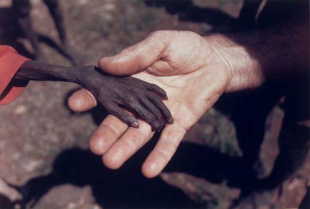 holding hands black and white photography. This example of emotive imagery is of child in Uganda holding hands with a